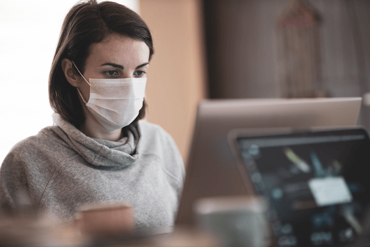 A woman works in the office and wears a mask